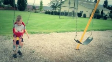 Brother pushing toddler on a swing — Stock Video