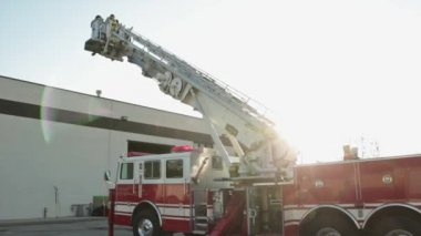 Firefighters on firetruck ladder — Stock Video