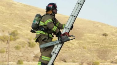 Firefighter climbing on firetruck ladder — Stock Video