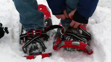A man straps on his snowshoes — Stock Video