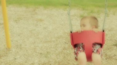 Toddler playing on the swingset — Stock Video