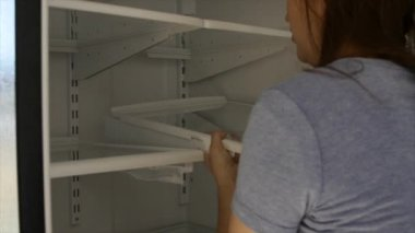 Woman putting fridge shelf back in after cleaning — Stock video