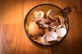 Su bardağı kırık yumurta kabukları dolu — Stok fotoğraf