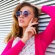 Outdoor fashion portrait of young beautiful brunette woman with natural make up and sexy lips, wearing stylish hipster summer pink outfit and retro pink sunglasses, urban white background. — Stock Photo #79272194