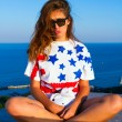 Summer cute portrait of young teen girl having fun and go crazy, wearing trendy top with american flag print,hat, hipster mirrored glasses. Sitting on the terrace with amazing sea view. Joy Sea Sunset — Stock Photo #79272242