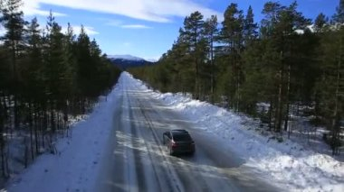 The car rides on a winter road among the woods and mountains — Stockvideo