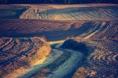 Vintage photo of sandy rural road and plowed fields — Stock Photo