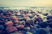 Vintage photo of rocky sea shore at sunset — Stock Photo