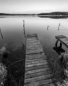 Black and white lake landscape with small wooden pier — Stock Photo