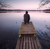Lake landscape with small wooden pier and man silhouette — Stock Photo