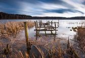 Lake landscape with small old wooden pier photographed on long exposure — Stock Photo