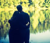 Silhouettes of hugging couple against the sunset sky — Stock Photo