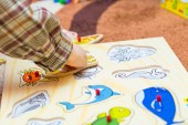 Child putting puzzle on  floor — Stock Photo