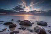 Beautiful rocky sea shore at sunrise or sunset. — Stock Photo