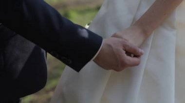 Gently connected hands of a newly-married couple with wedding rings on a finger on a background of a white wedding dress — ストックビデオ