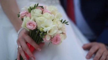 Hands of the bride and groom with rings on a beautiful wedding bouquet — Stock Video