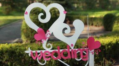 Bröllop inredning. Trä plack med inskriptionen bröllop. Bröllop på en tallrik grön bakgrund och en fontän. — Stockvideo