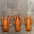 Three red crayfishes in a row on old wooden table — Stock Photo #69576151