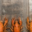 Three red crayfishes in a row on old wooden table close-up — Stock Photo #69576213