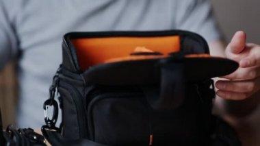 Guy packt eine Tasche für Foto-Ausrüstung — Stockvideo