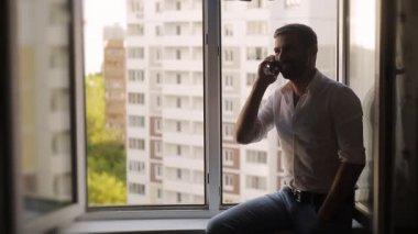Man talking on the phone sitting on the windowsill — Stock Video