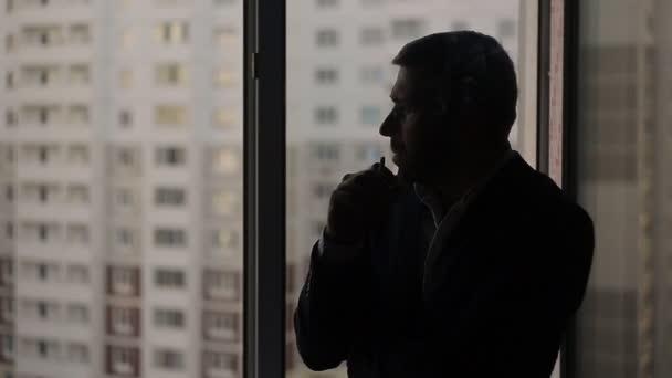 Un hombre en un traje con un cigarrillo en la ventana — Vídeo de stock