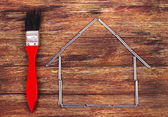 Shape of a home building and brush - Stock Image — Stock Photo