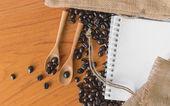 Białe notatnik pod kątem twój tekst z wory i kawa na drewnianą łyżką. — Zdjęcie stockowe