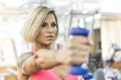 Young woman working triceps exercise at gym — Stock Photo