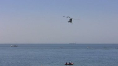 Helicopter flying sideways at low altitude over water — Stock Video