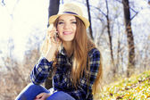 Beautiful young blonde in a hat with a phone — Stock Photo