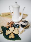 Teapot, cookies, walnuts and cup of coffee — Stock Photo