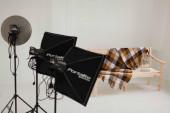 Houten bench met deken en verlichtingsapparatuur in fotostudio — Stockfoto