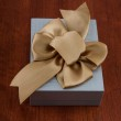 Holiday Gift Packed into Grey Box with Ribbon on Glossy Wooden T — Stock Photo #71133047