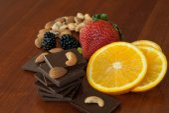Chocolate, nuts, berries and orange — Stock Photo