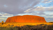 Sunset at Uluru Ayers Rock with red color and clouds — Stock Photo