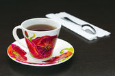 Cup of tea with poppies and spoon — Foto de Stock