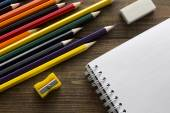 Crayons, notebook , eraser and pencil sharpener — Stock Photo