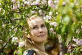 Krásná blonďatá dívka v kvetoucí zahradě — Stock fotografie