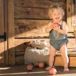 Happy Baby Girl sitting near Wooden countryside Barn — Stock Photo #77504752