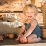 Happy Baby Girl sitting near Wooden countryside Barn — Stock Photo #77504756