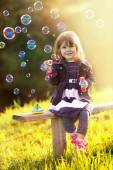 Portrait of a girl sitting on a wooden bench blows bubbles in th — Stock Photo