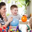 Woman with two children playing with balloons — Stock Photo #68343471