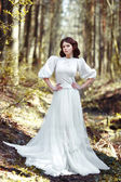 Beautiful girl in a white dress in the forest — Stock Photo