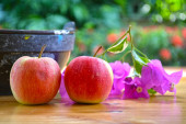 Apples and flowers on table — Stock Photo