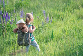 Girl with teddy bear in backpack in tall grass — Stock Photo