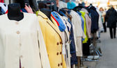 Row of mannequins with different coloured women's clothes on mar — Stock Photo