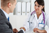 Beautiful smiling female medicine doctor shaking hands with male — Stock Photo