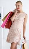 Beautiful smiling walking woman wearing dress holding colored pa — Stock Photo