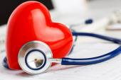 Medical stethoscope and red toy heart lying on cardiogram chart — Stock Photo